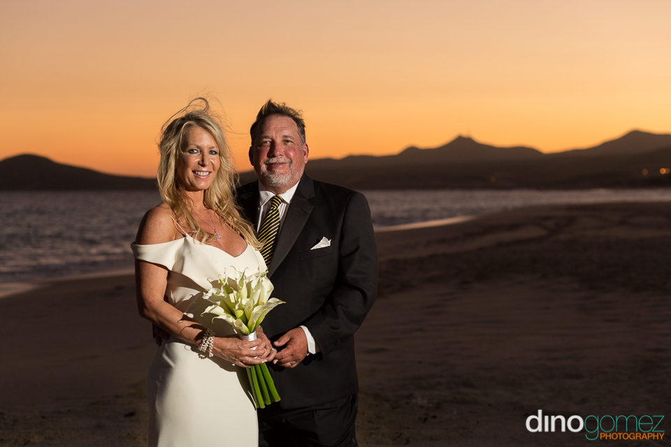 Los Cabos beach side wedding couple embrace