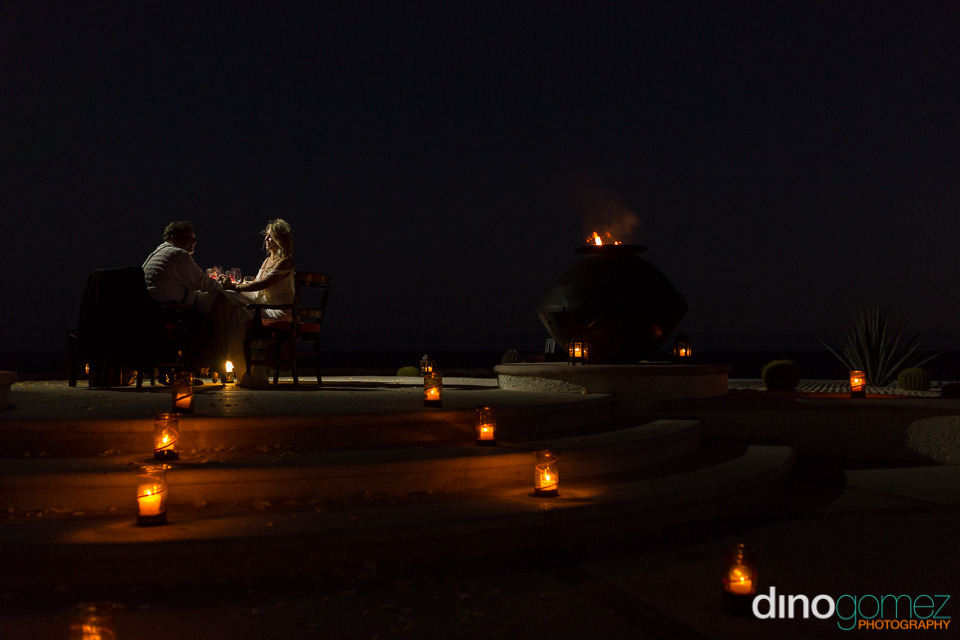 Bride and groom sharing a romantic dinner with candles on their wedding anniversary