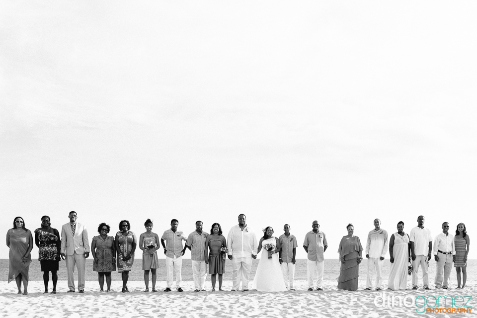 Destination wedding couple and guests standing in a line on the beach in Los Cabos