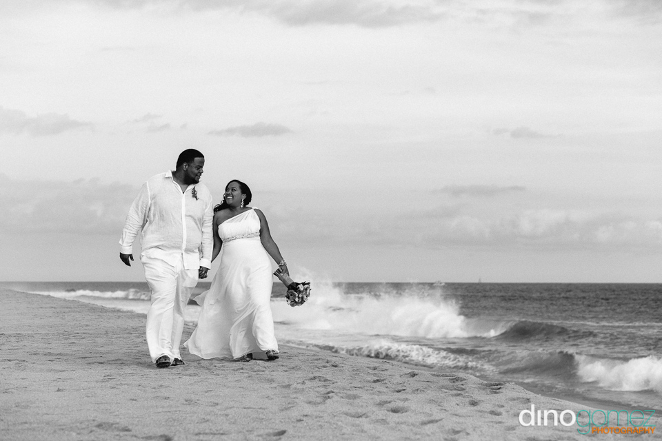 Bride and groom holding hands and strolling on the beach