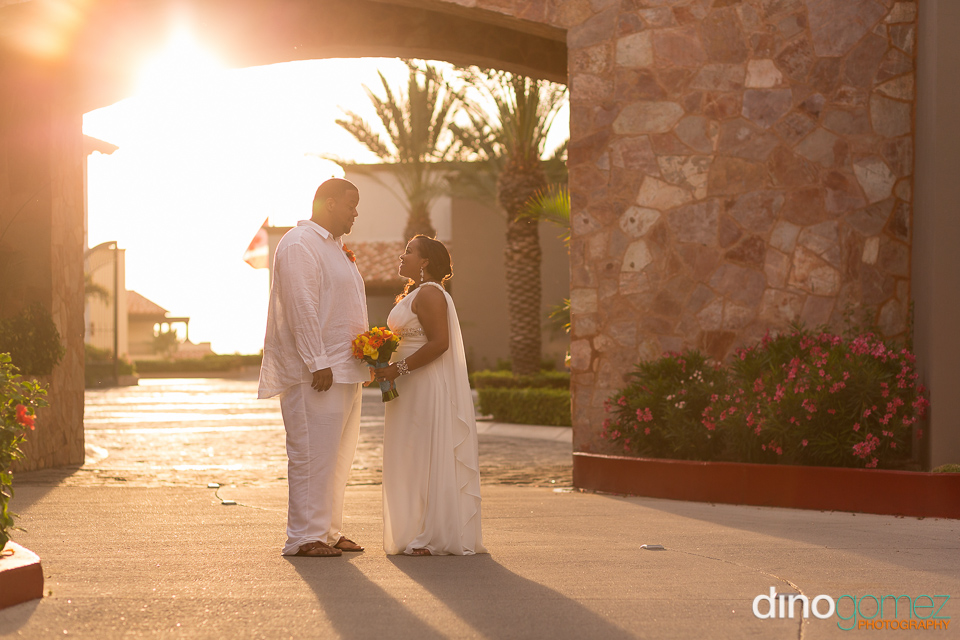 Couple looking at each other at sunset captured by destination wedding photographer in Cabo Dino Gomez