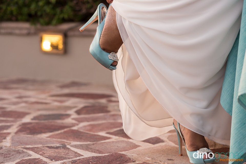Bride slipping on her blue slingback shoes