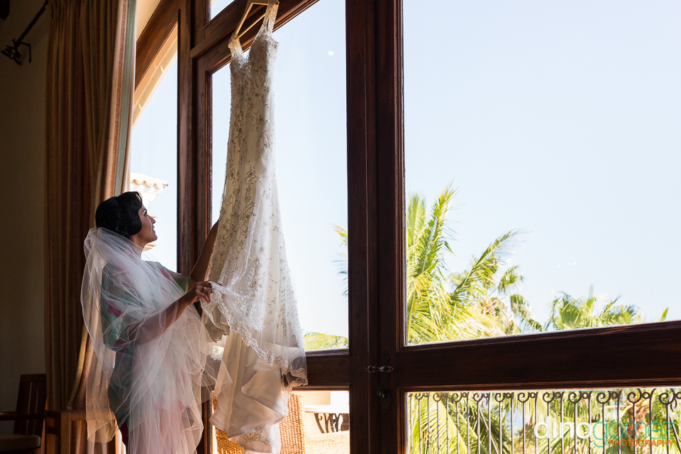 The bride grabs her wedding dress hanging by the door in Mexico
