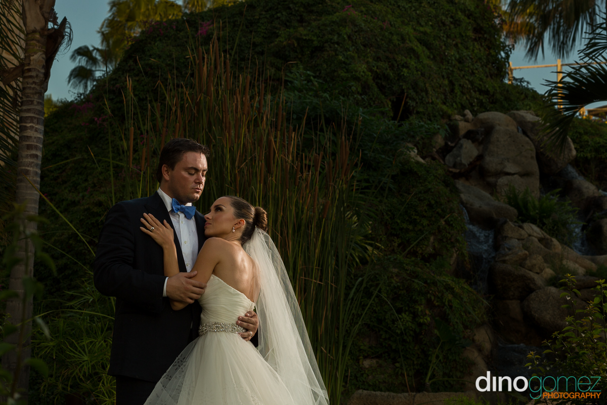 Dramatic snap of the bride and groom embracing in the lush garden by photographer in Cancun Dino Gomez