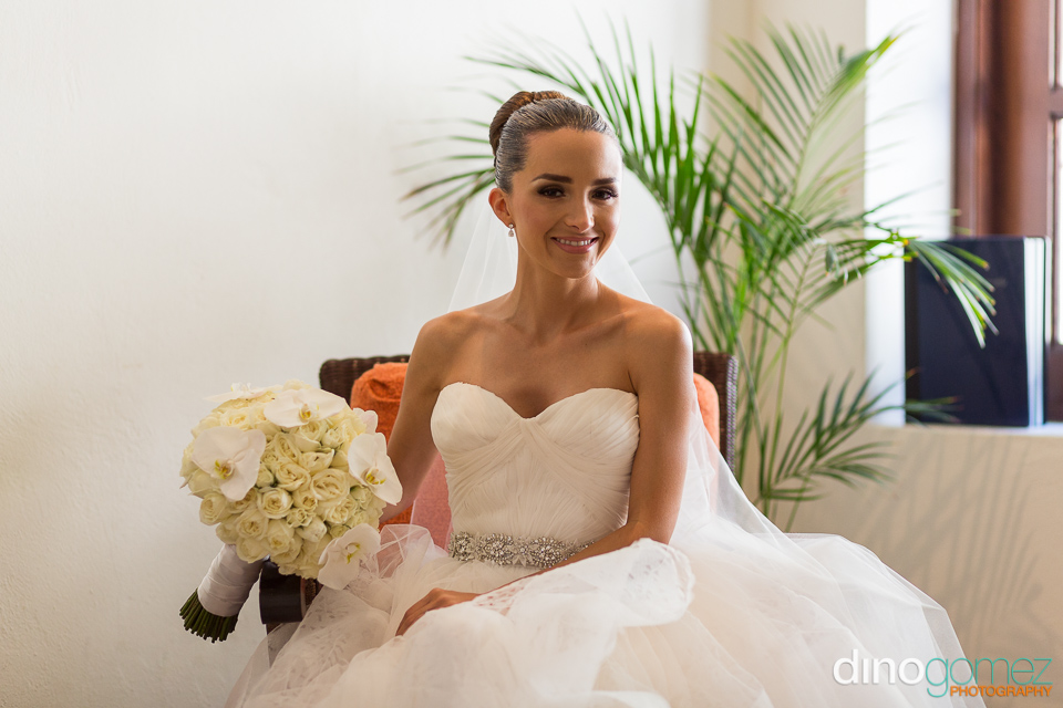 A happy bride sitting elegantly with her wedding bouquet