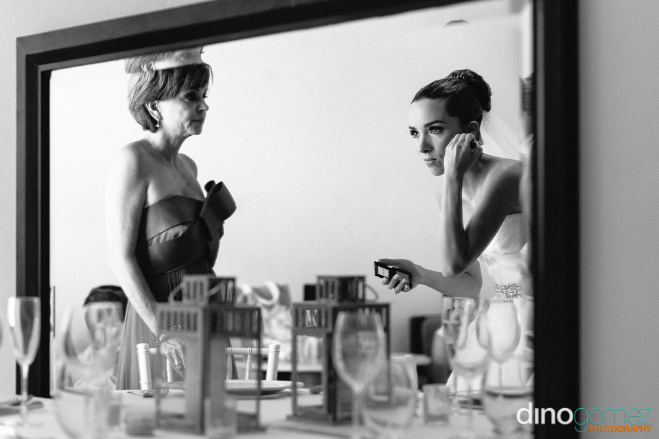 Bride fixing her earring while looking in the mirror