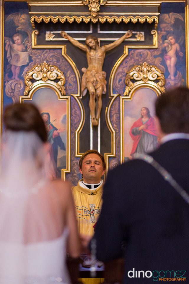 The pastor praying during the wedding ceremony with the bride and groom out of focus
