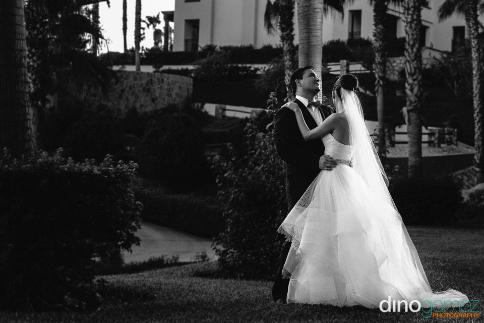 Newlyweds embracing each other in black and white out on the lawn