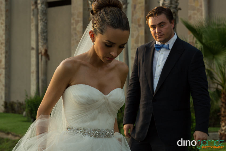 A closeup of the bride looking down and the groom in the background by wedding photographer Dino Gomez