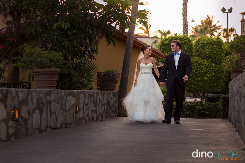 A cute couple holding hands as they walk down the street after getting married in Mexico