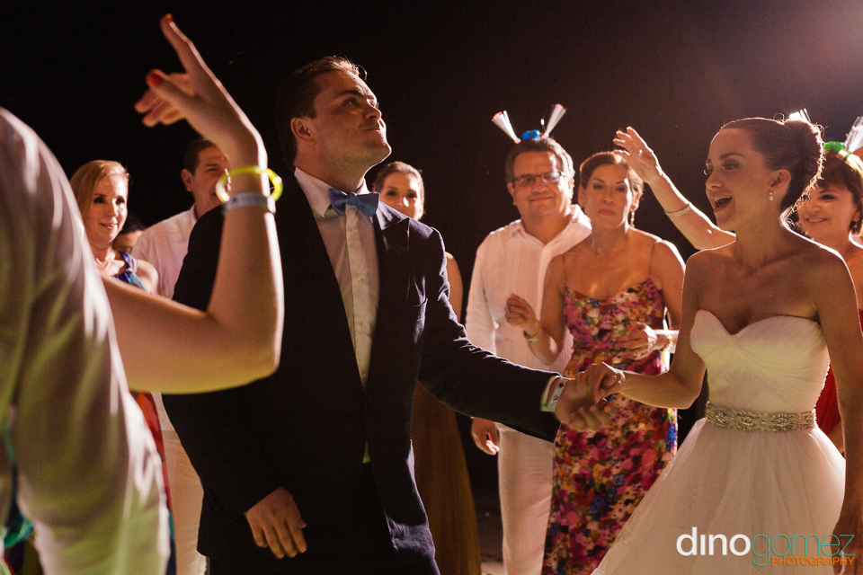 Cute wedding couple having fun on the dance floor with their guests looking on