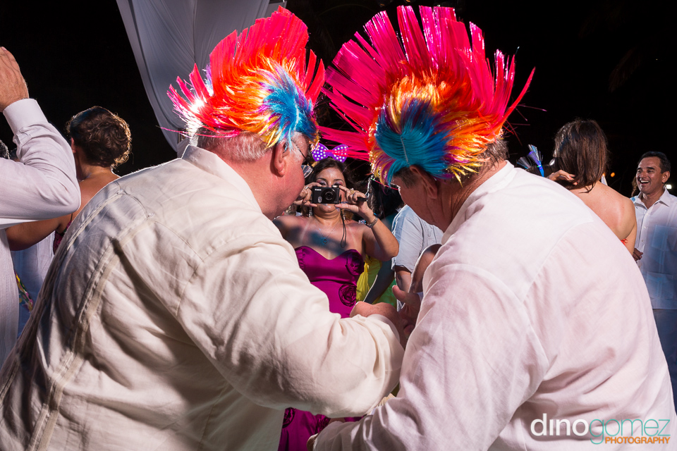 Back view of an elderly couple in fashion punk wigs at a destination wedding