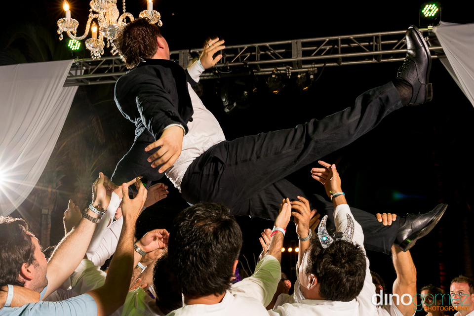 A snap of the groom being tossed into the air by wedding photographer Dino Gomez
