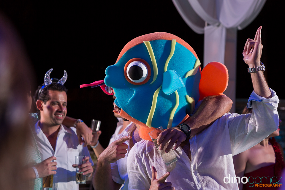 A wedding guest wearing a colourful fish head gear
