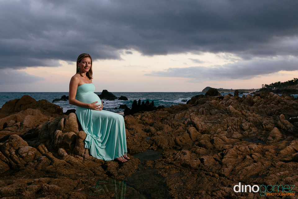 Cute pregnancy picture at the beach with the mom to be sitting on rocks