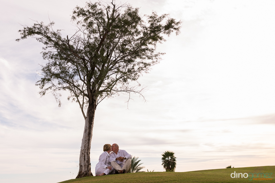 Couple kissing on the grass under a tree on the golf course