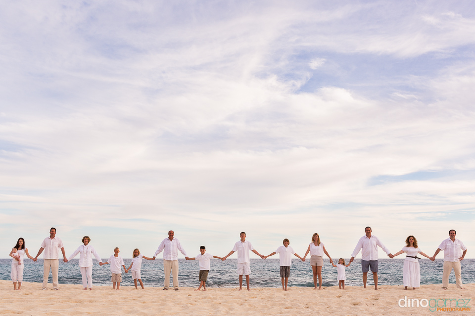 Family holding hands on the beach with the ocean in the background