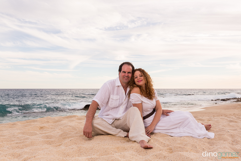 Couple sitting together on the sand by sea