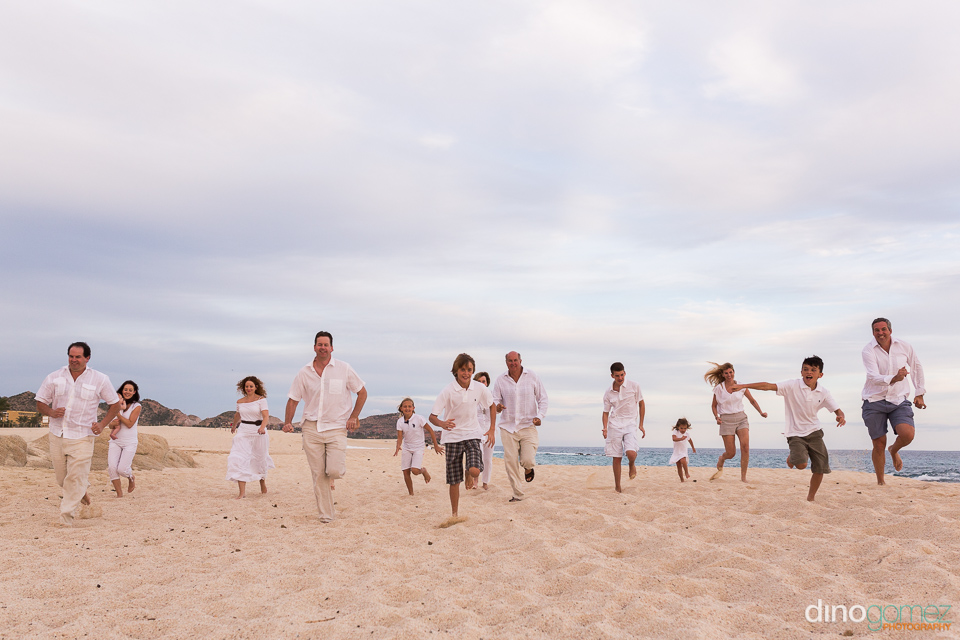 Family with kids and grandparents running on the beach