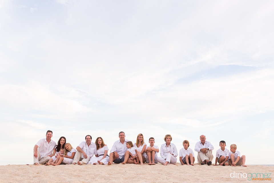 Large mixed family pose on a beach in Mexico