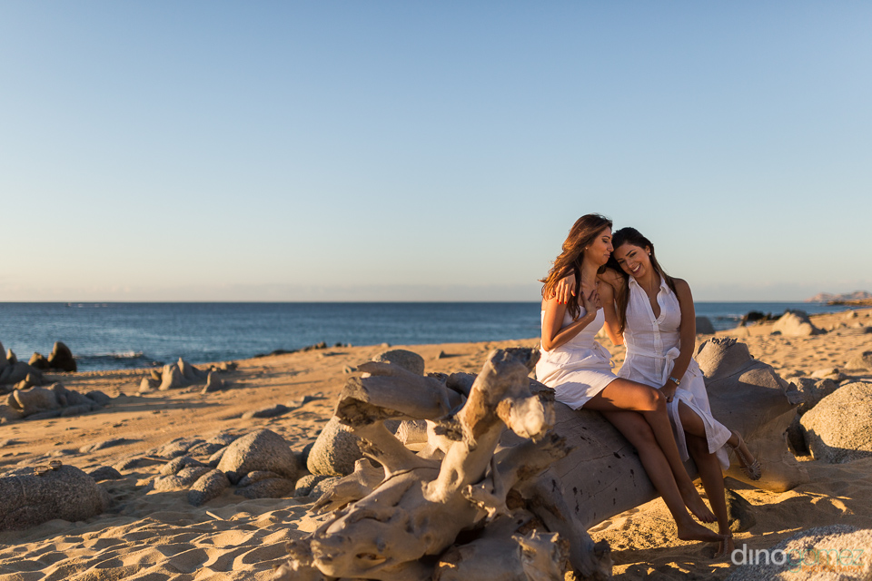 Sisters in white dresses sitting on a beach log in Mexico