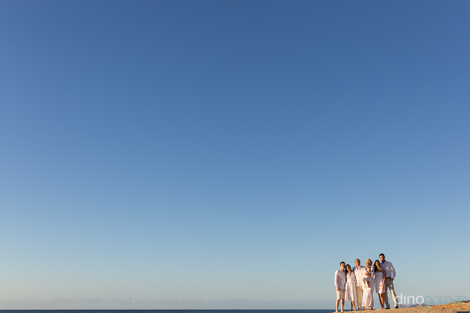 Beautiful beach family photo with everyone dressed in white in Mexico