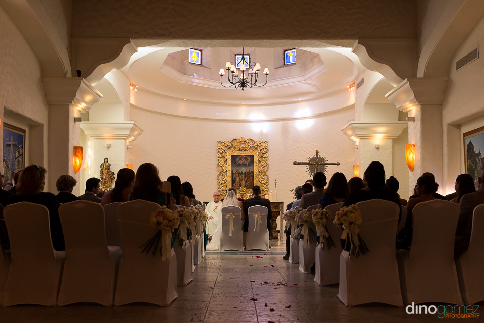 The bride and groom sitting at the altar during the ceremony in front of the priest and a golden wall painting