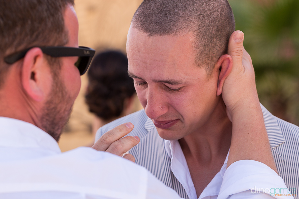 Crying groom being comforted by one of his groomsmen before the wedding