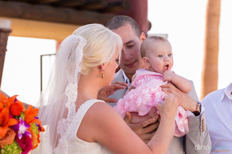 Cute snap of the newlyweds holding a baby girl courtesy of destination wedding photographer Dino Gomez