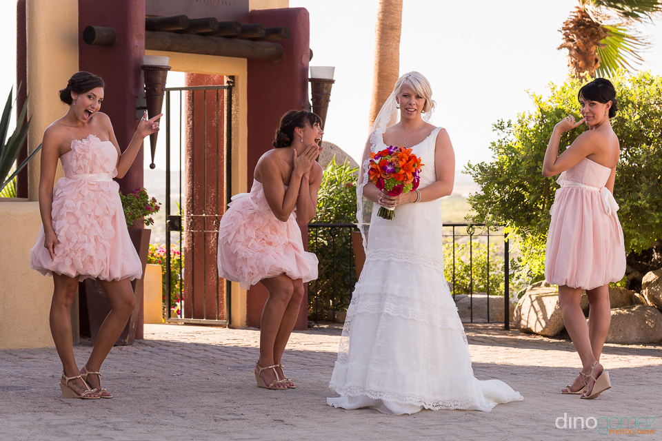 Cute wedding shot of the bridesmaids making fun poses with the bride at her Mexico destination wedding