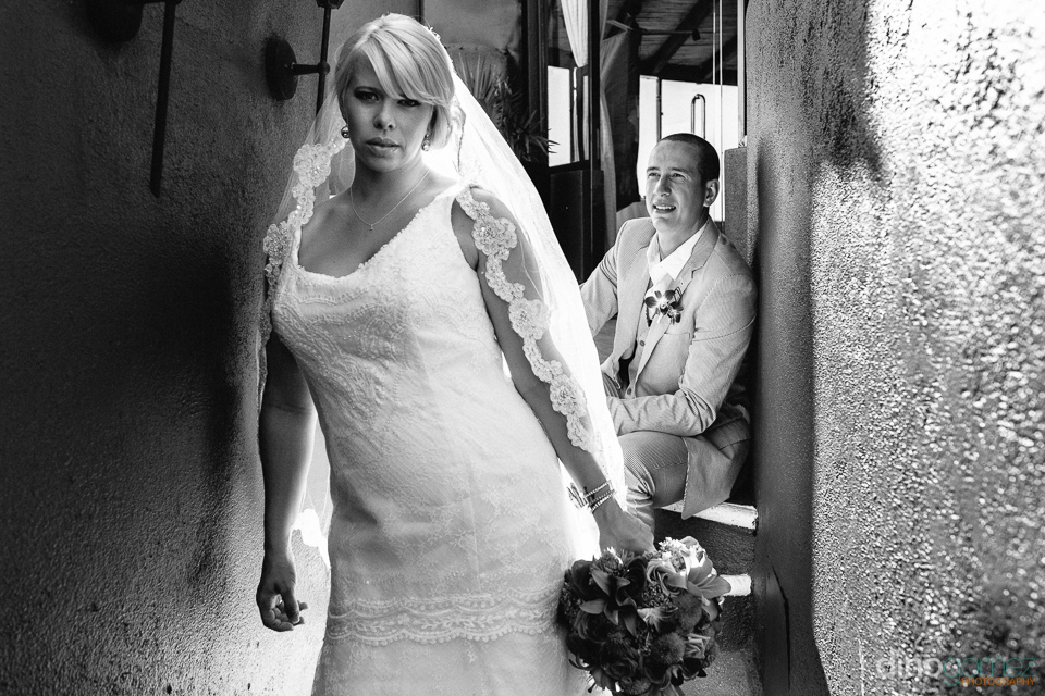 Black and white shot of the bride posing in a narrow stairway and the groom sitting in the background by wedding photographer Dino Gomez