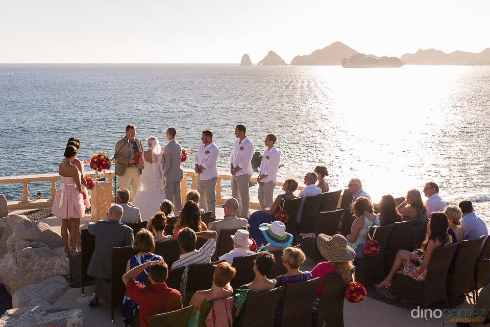 Awesome shot of the wedding couple getting married with their guests and the magnificent ocean in the background by wedding photographer in Cabo Dino Gomez
