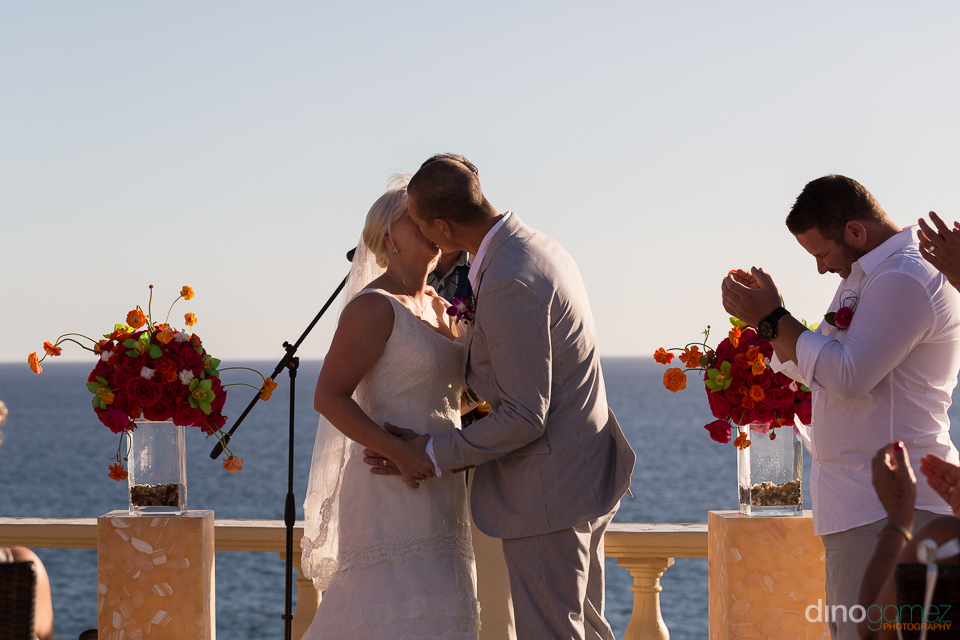 The groom kissing his new wife during their destination wedding ceremony in Mexico