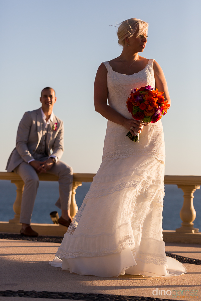 Profile of a bride standing with her bouquet of flowers and the groom sitting on a ledge by wedding photographer Dino Gomez