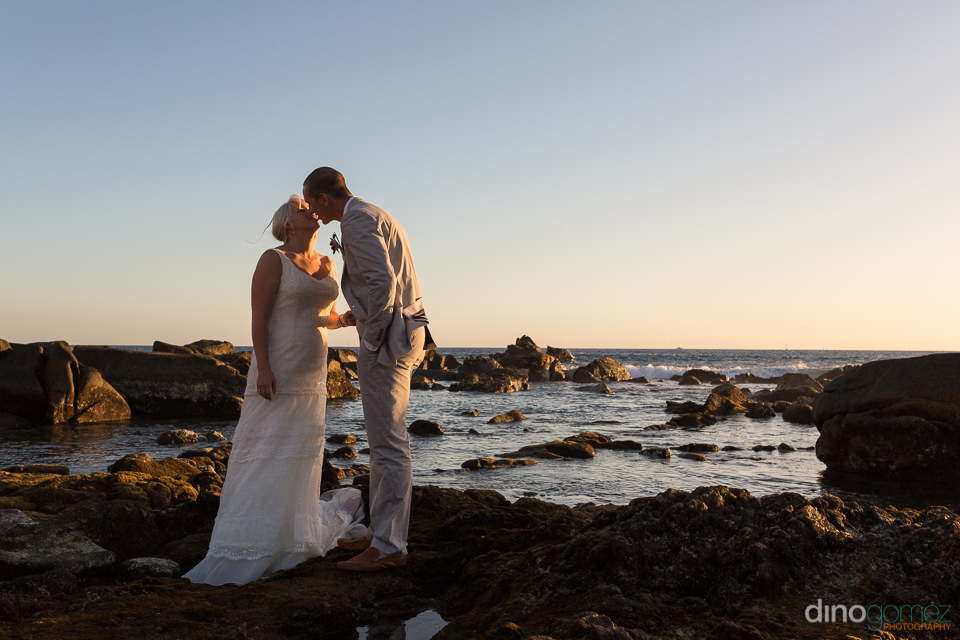 Wedding snap shot of the newlyweds kissing on a rocky beach at sunset in Mexico
