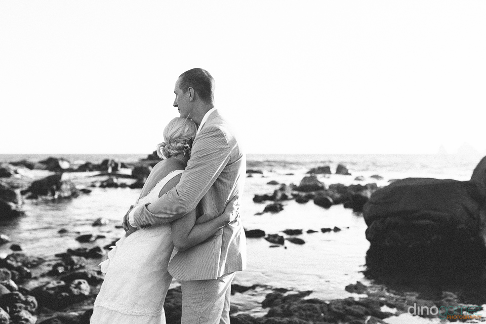 Newlyweds hugging on the rocky beach after the wedding ceremony