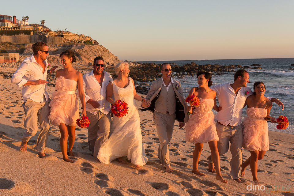 Wedding party walking and laughing on the beach by the talented wedding photographer in Mexico Dino Gomez