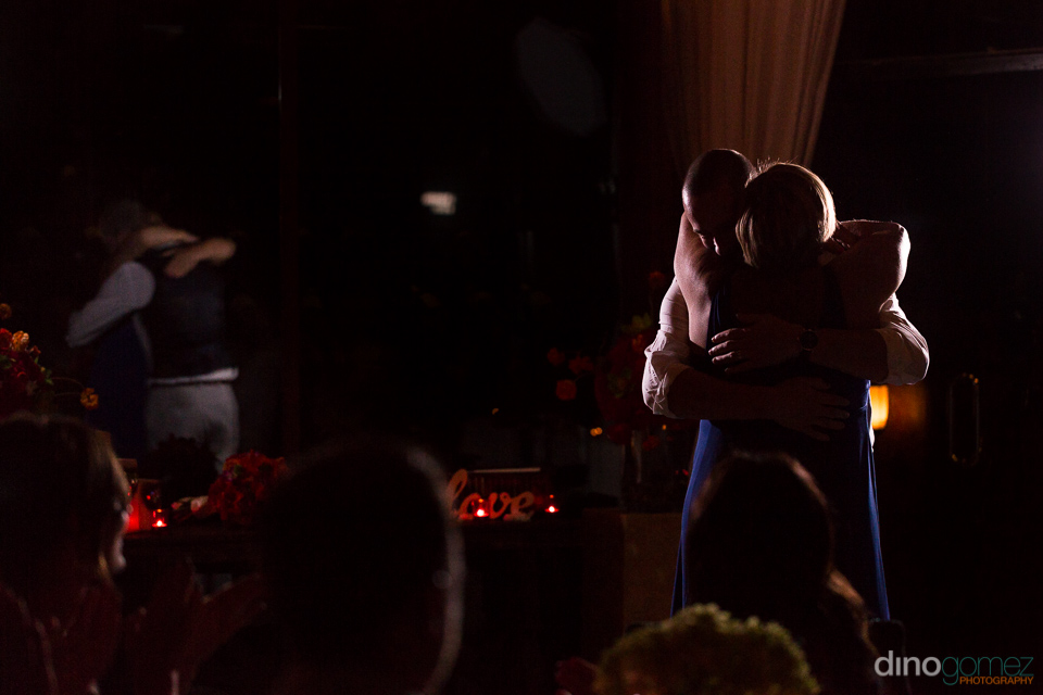 Beautiful shot of the groom hugging his mom in a blue dress at the wedding reception