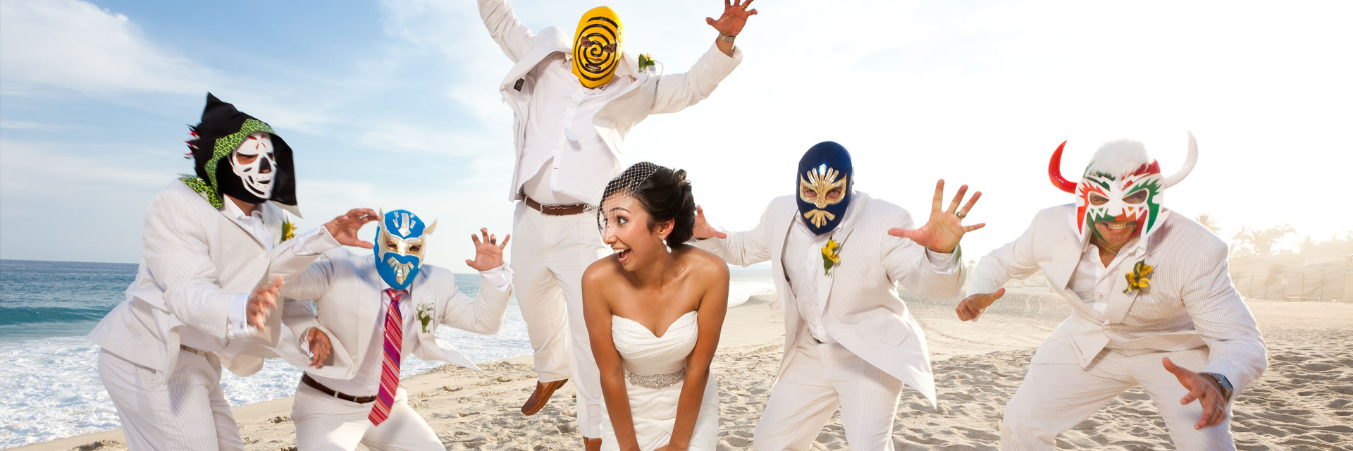 A startled bride looks shocked as the groomsmen jump around in mexican wrestling masks. Photography was taken by Dino Gomez