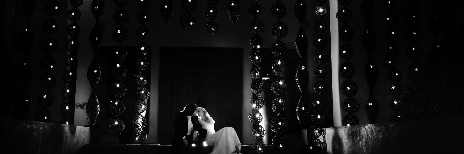 Black and white shot of the wedding couple kissing on the stairs