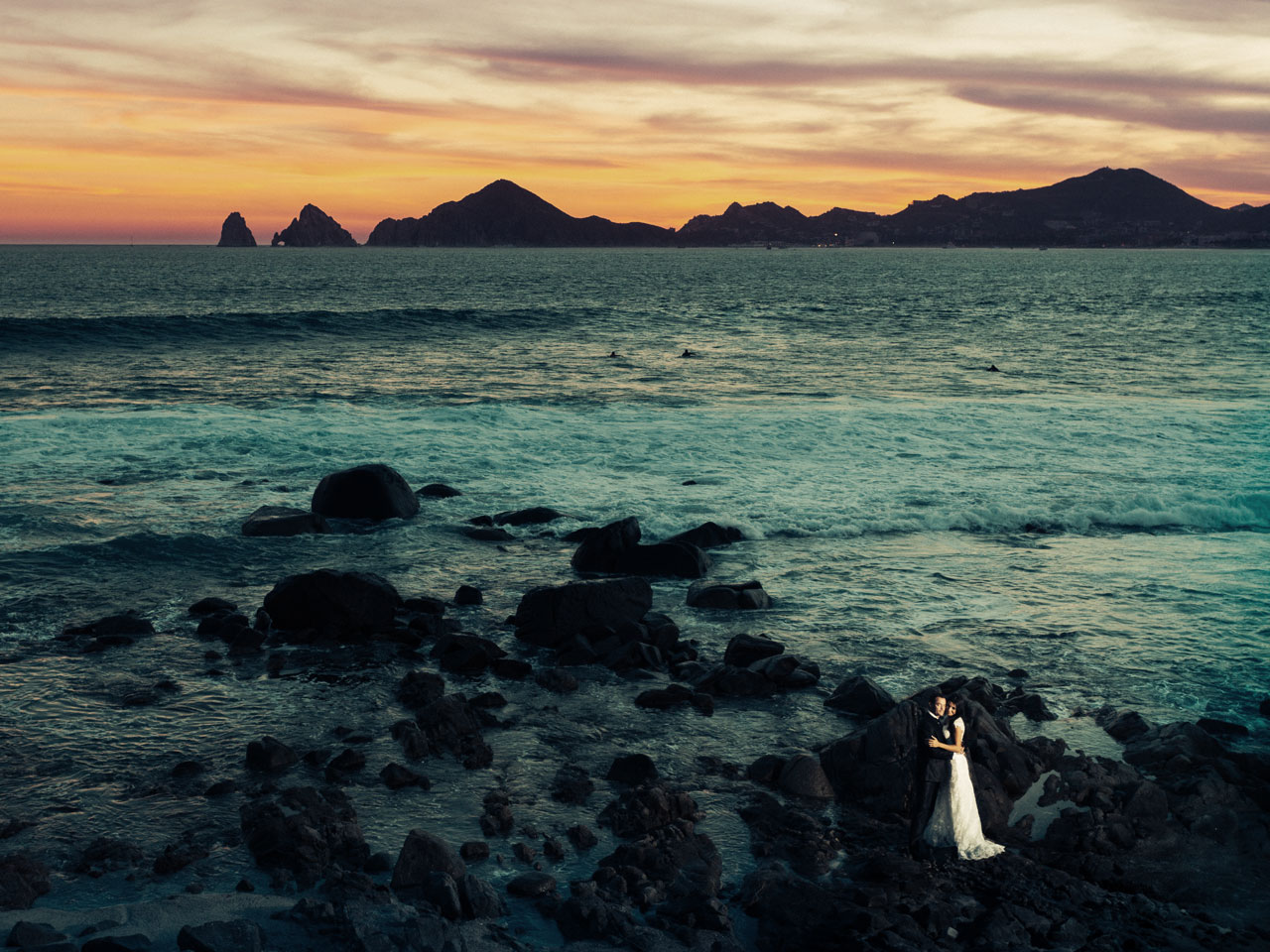 An aerial shot of the wedding couple embracing on the rocky beach