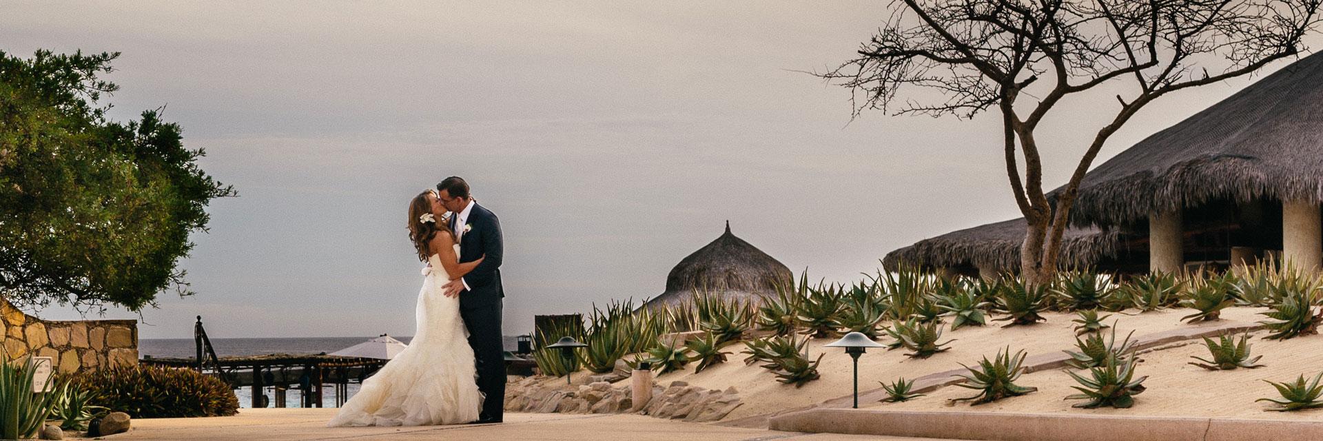 Wedding couple sharing a kiss on a beach path in Mexico