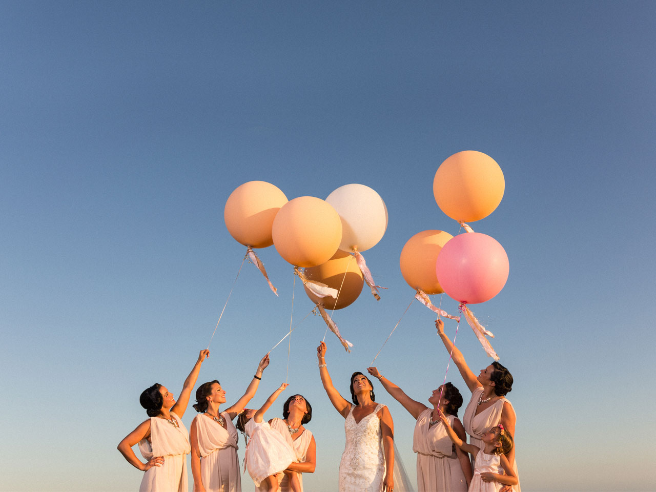 A snap shot of the bride and her bridesmaids releasing balloons on the beach in Mexico