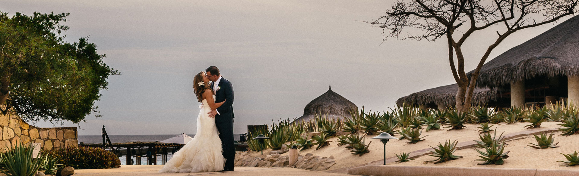 Wedding couple sharing a kiss on a beach path in Mexico