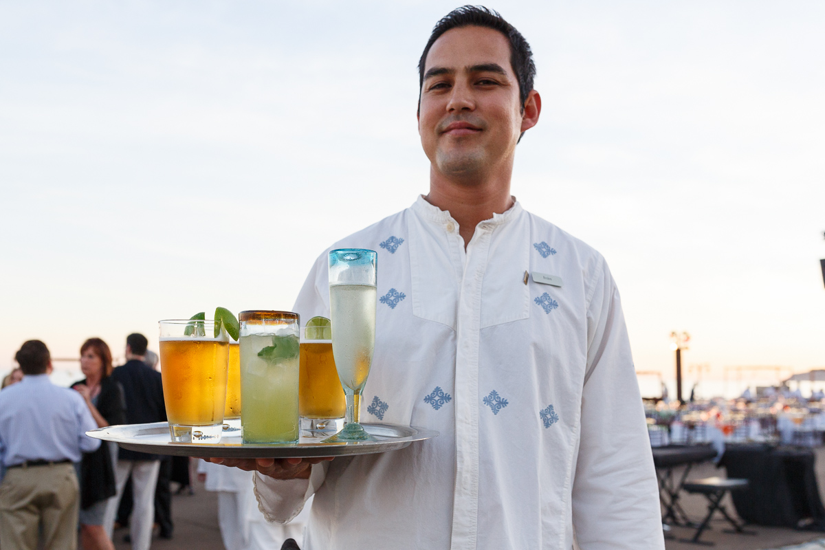 A shot of a waiter carrying drinks on silver platter by wedding photographer in Cabo Dino Gomez
