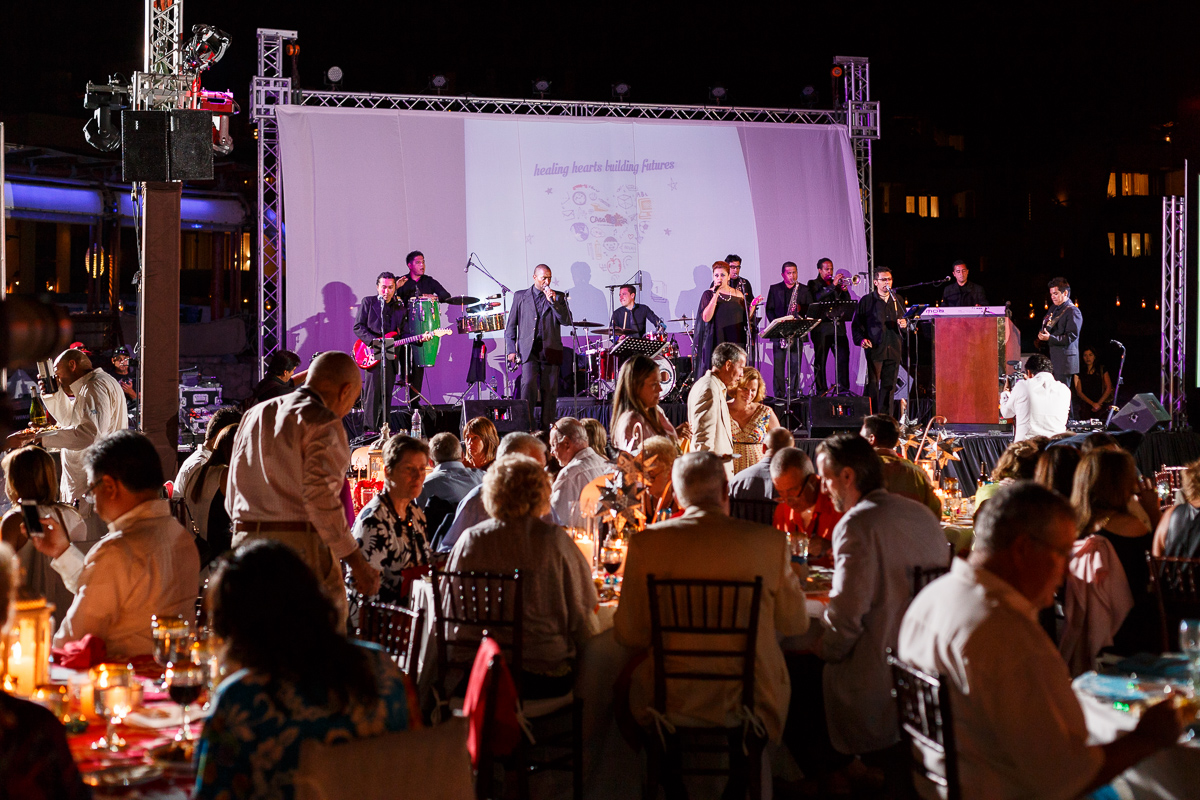 Candid Shot Of The Performers On Stage And The Guests Sitting At Their Tables At An Event In Mexico