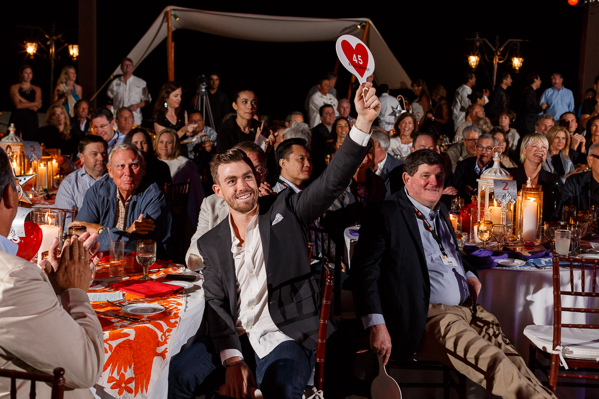 A snapshot of a happy man with an auction paddle in a crowd at an event in Mexico