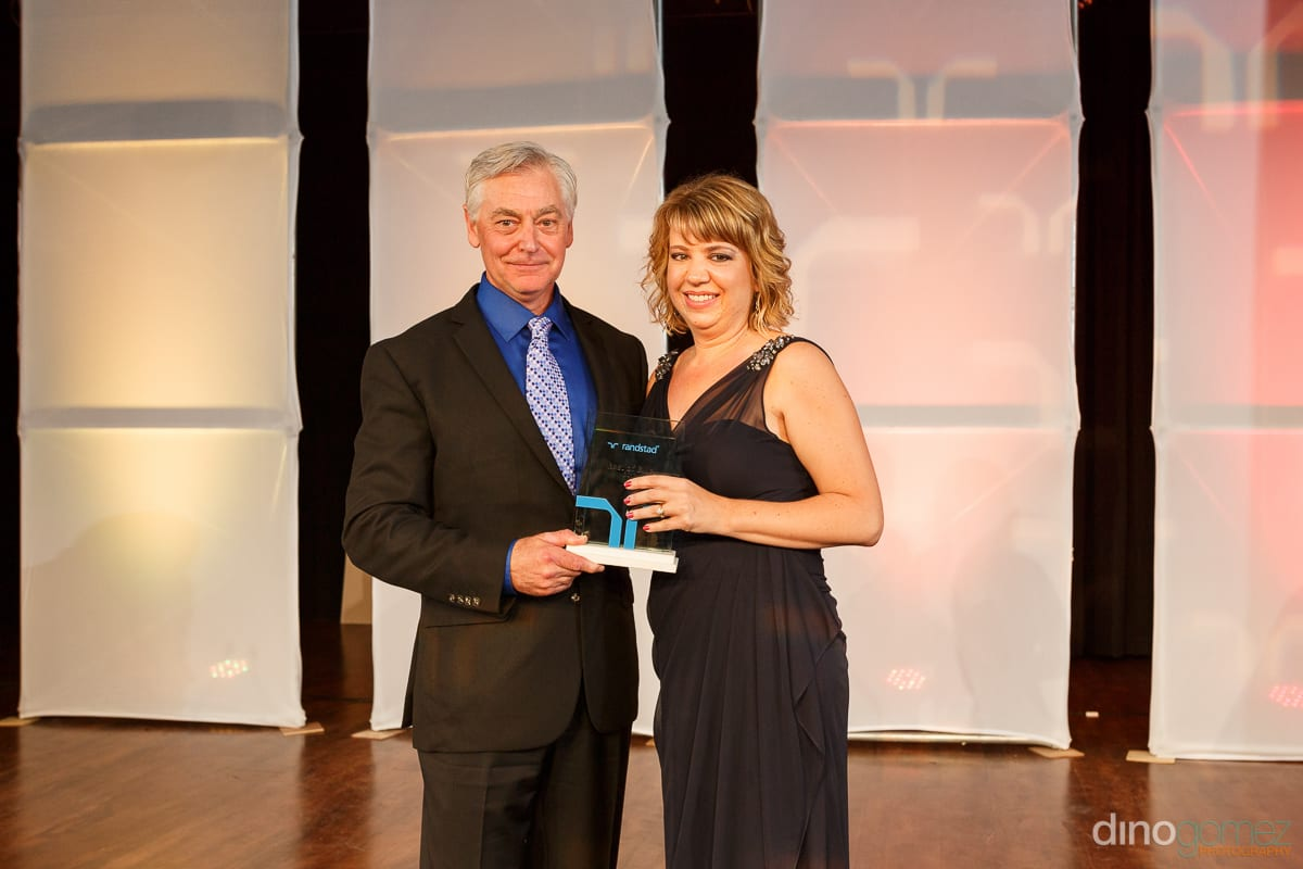 A well-dressed gentleman presenting an award to a woman in a beautiful gown at Randstad Cabo 2014 - Secrets Pue