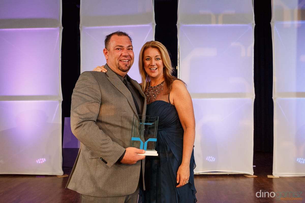 A happy man receiving an award at Randstad Cabo 2014 - Secrets Pue from a smiling woman in a blue gown.
