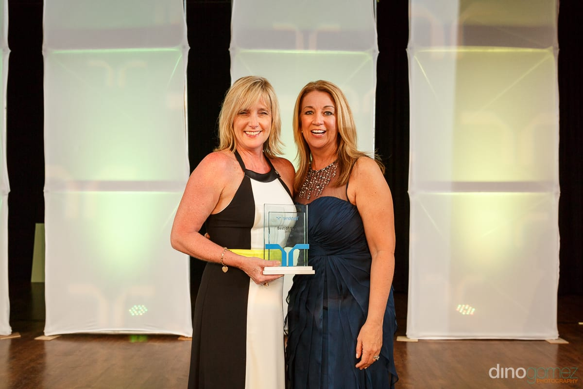 Two women in stunning ball gowns holding an award at Randstad Cabo 2014 - Secrets Pue taken by Dino Gomez